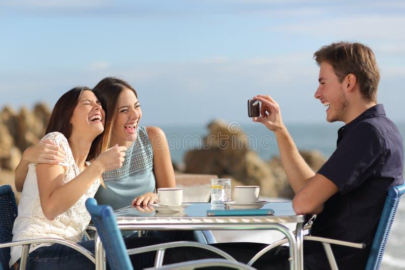 Vrienden die en foto met een slimme telefoon nemen lachen stock foto