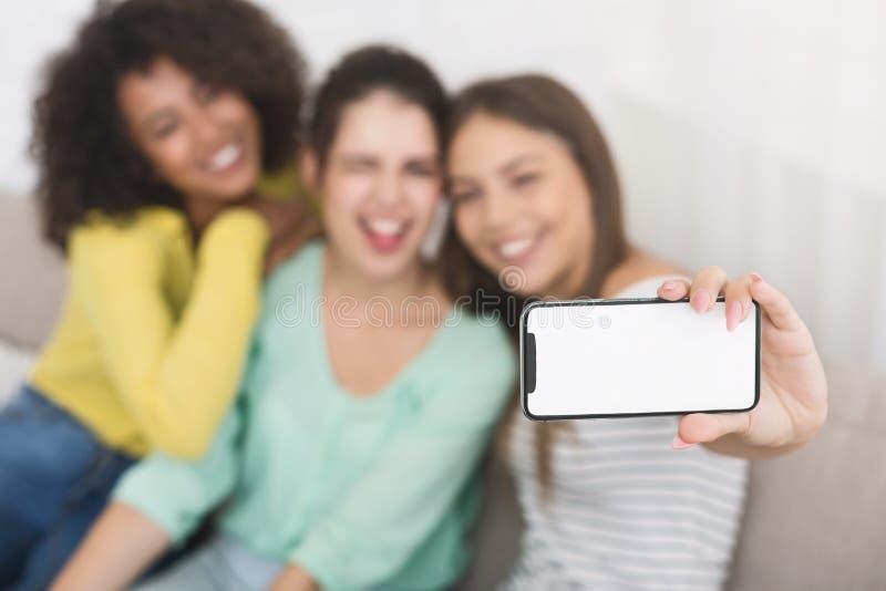 Vrienden die en foto's op smartphone maken grimassen trekken stock afbeelding