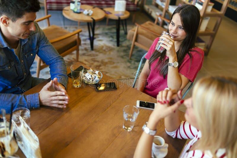 Vrienden die en in koffie roddelen babbelen royalty-vrije stock foto