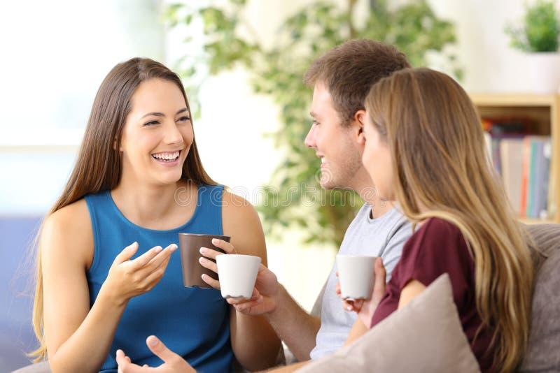 Vrienden die en koffie thuis spreken drinken stock foto