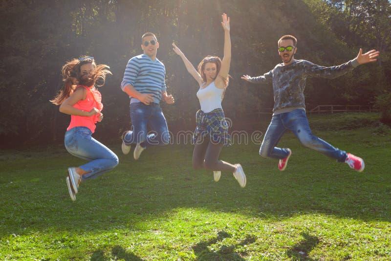 Vrienden die en pret springen hebben bij zonnige dag royalty-vrije stock fotografie