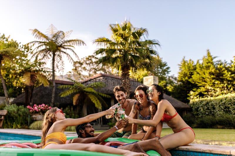 Vrienden die en van bieren genieten roosteren bij poolpartij royalty-vrije stock fotografie