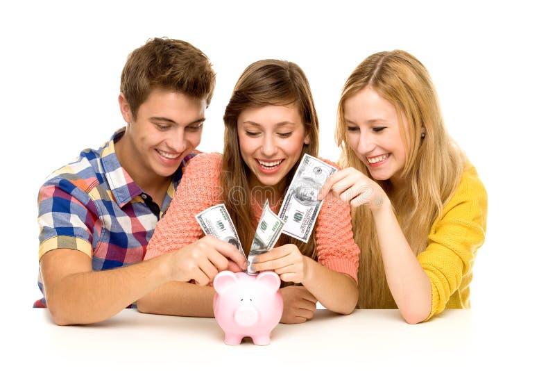 Vrienden die geld in spaarvarken zetten stock afbeeldingen