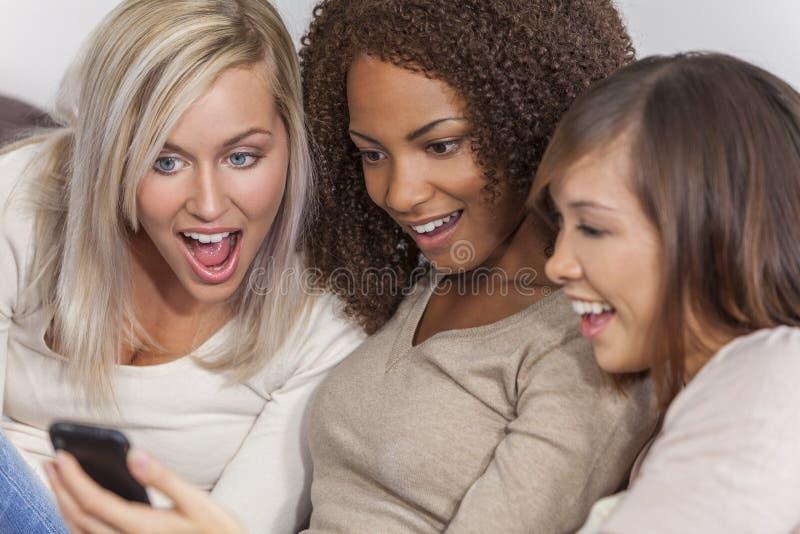 Vrienden die Groeps van tussen verschillende rassen de Mooie Vrouwen Smartphone gebruiken royalty-vrije stock afbeeldingen