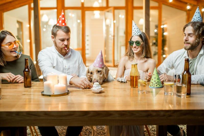 Vrienden die hond` s verjaardag vieren stock afbeeldingen