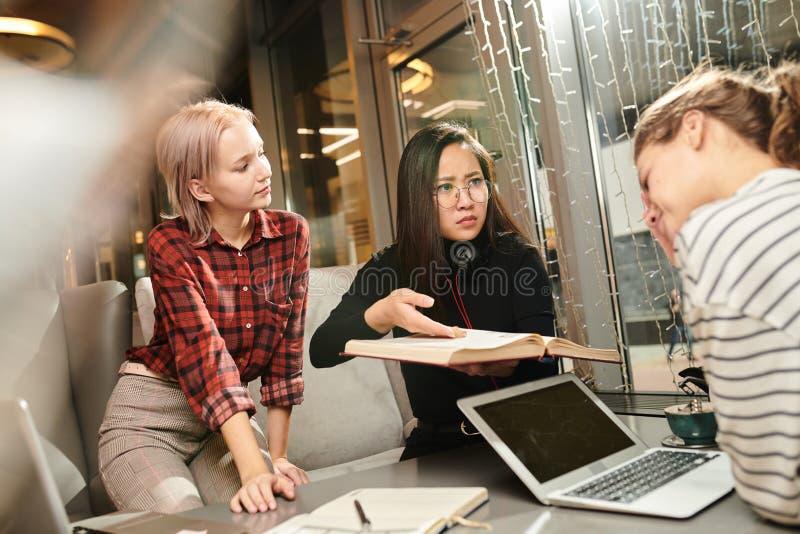Vrienden die in koffie bestuderen stock afbeeldingen