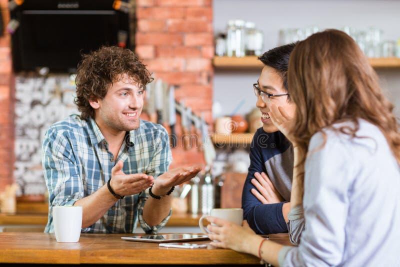 Vrienden die in koffie en het drinken koffie samenkomen royalty-vrije stock afbeelding