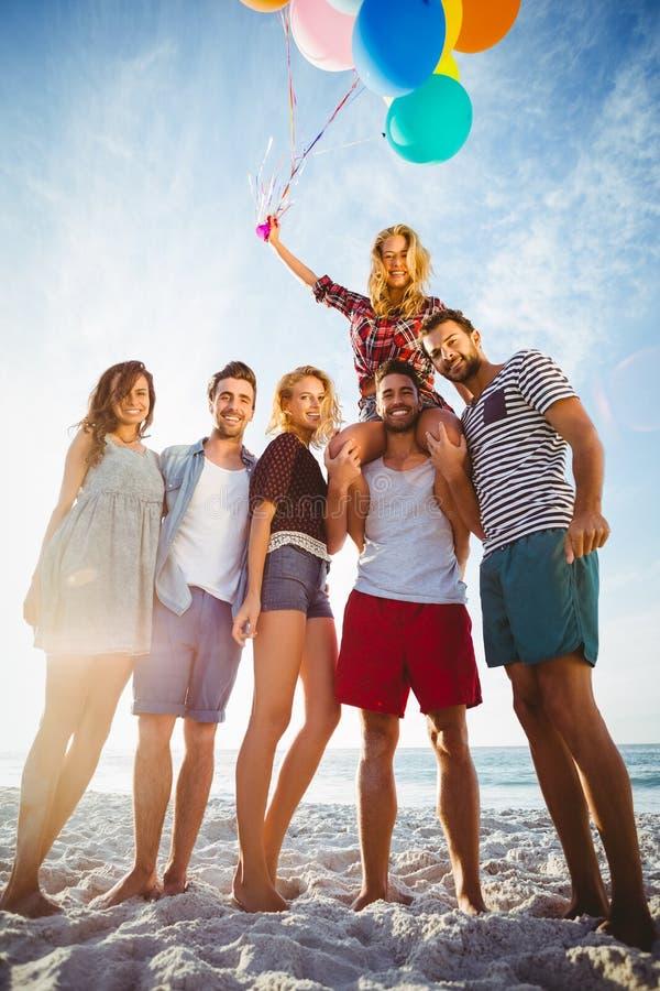 Vrienden die met ballon op zand stellen royalty-vrije stock foto