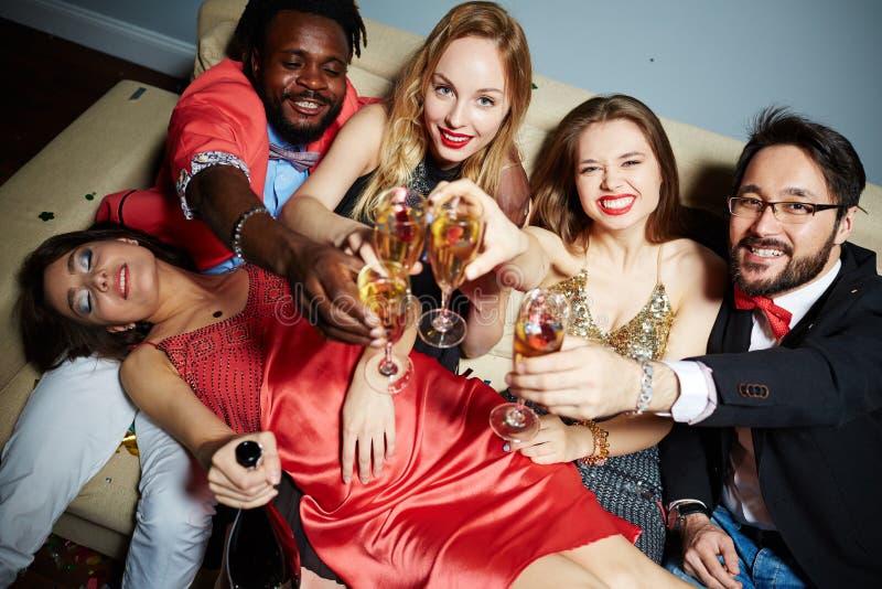 Vrienden die met champagnefluiten roosteren stock foto