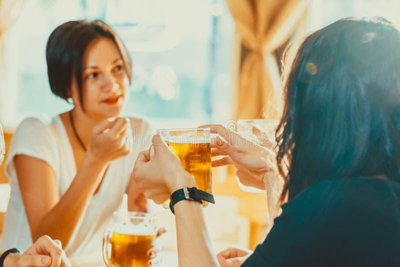 Vrienden die met glazen licht bier bij de bar roosteren stock foto