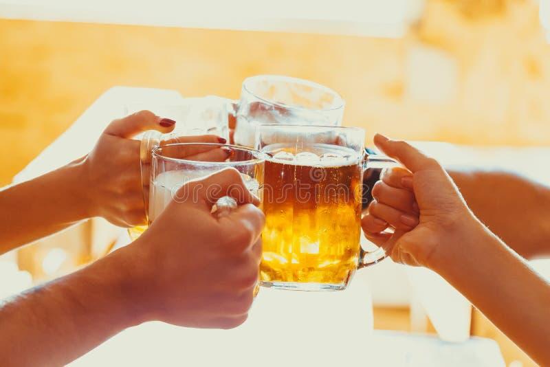 Vrienden die met glazen licht bier bij de bar roosteren stock fotografie