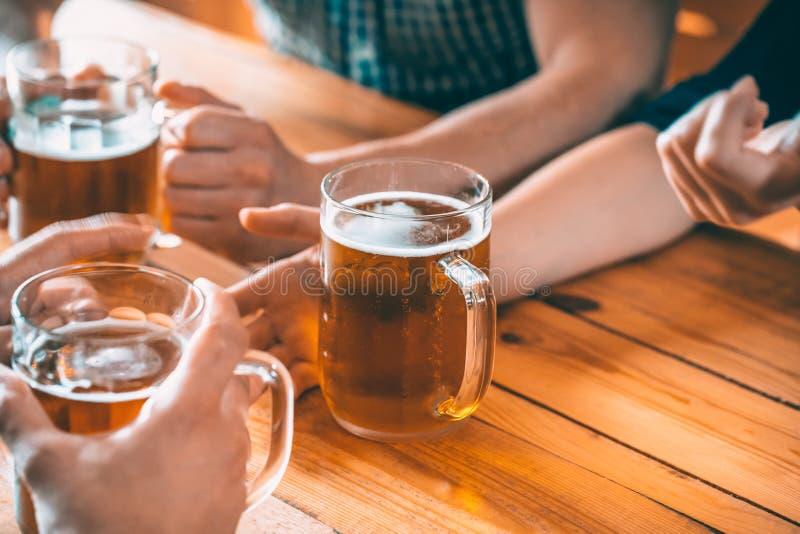 Vrienden die met glazen licht bier bij de bar roosteren Mooie achtergrond van Oktoberfest royalty-vrije stock afbeeldingen