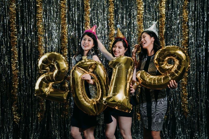 Vrienden die met 2019 gouden ballons dansen royalty-vrije stock afbeelding