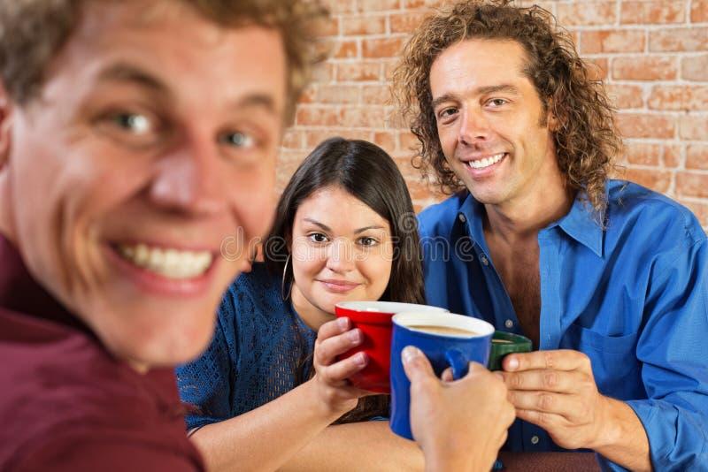 Vrienden die met Koffie roosteren stock foto