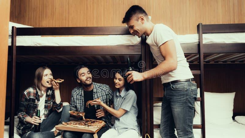Vrienden die op bed zitten die Pizza en drank eten stock afbeeldingen