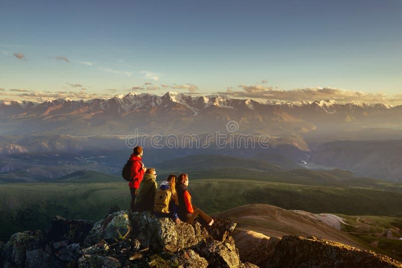 Vrienden die op bergbovenkant aan zonsondergang kijken stock foto