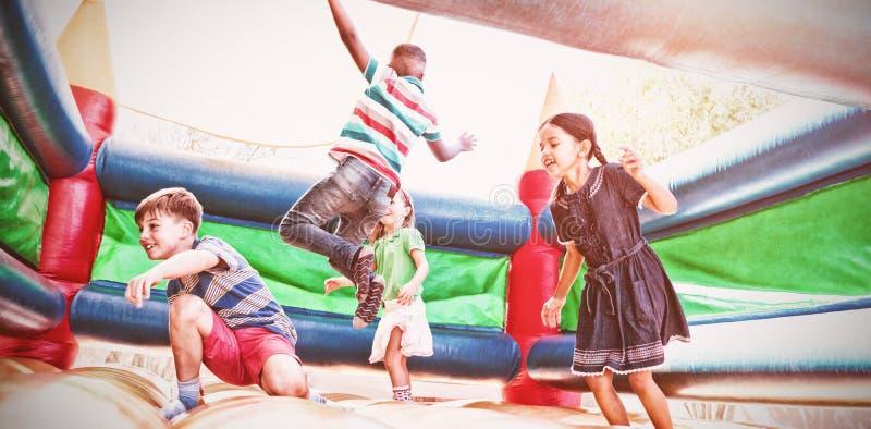 Vrienden die op bouncykasteel springen stock foto's