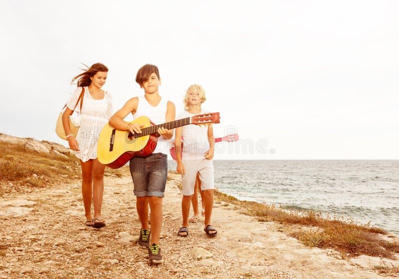 Vrienden die op de het strand en het spelen gitaar lopen royalty-vrije stock foto's