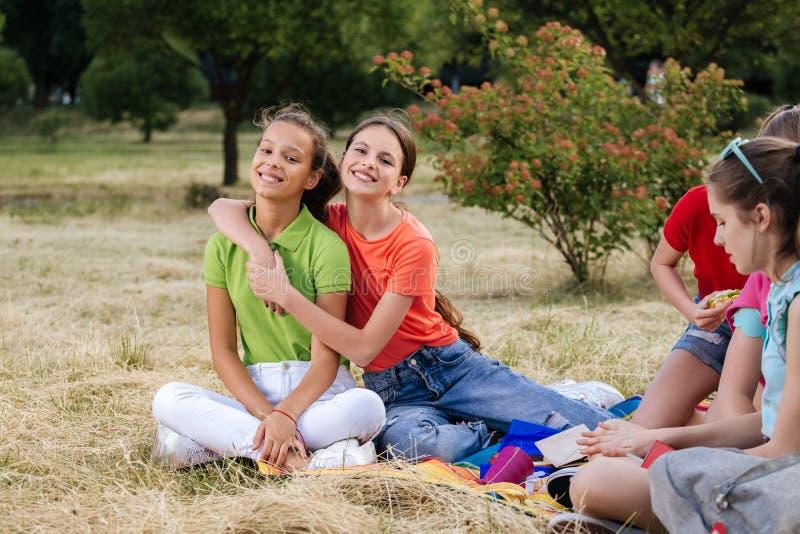 Vrienden die op het gras zitten die gezond voedsel eten bij een lunch stock afbeeldingen