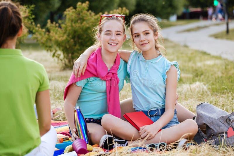 Vrienden die op het gras zitten die gezond voedsel eten bij een lunch royalty-vrije stock foto