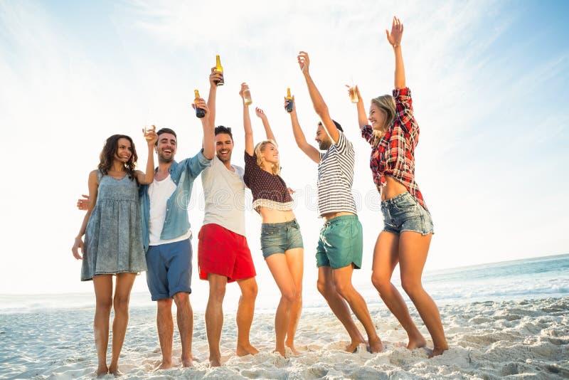Vrienden die op het strand roosteren stock foto's