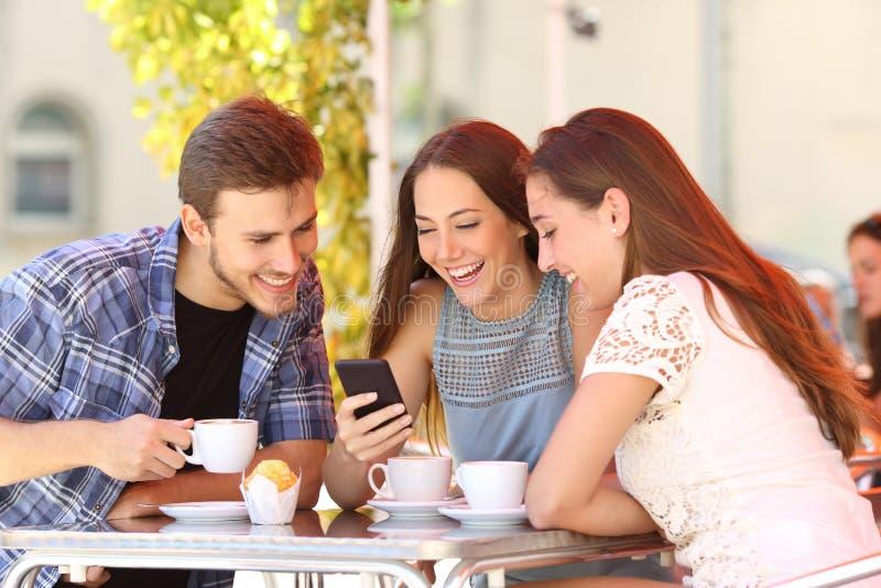 Vrienden die op media in een slimme telefoon in een koffiewinkel letten stock afbeeldingen