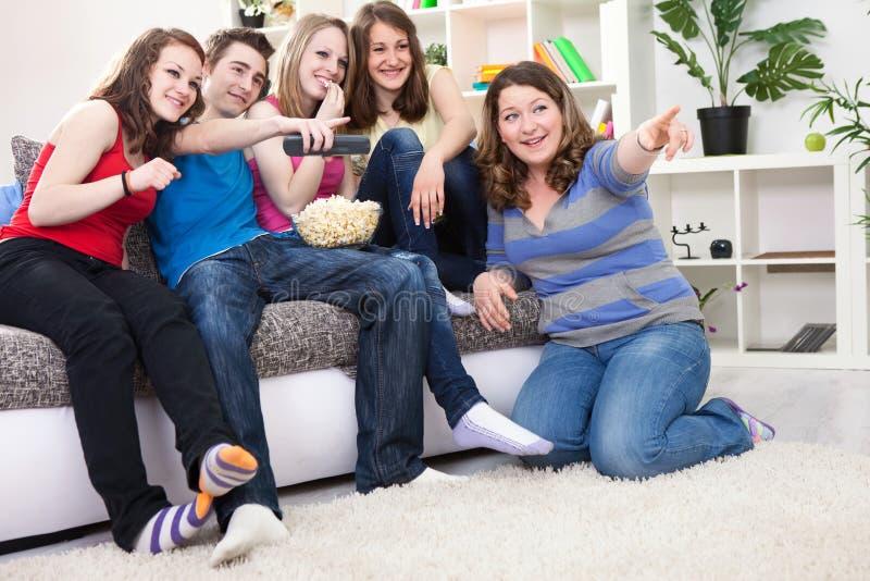 Vrienden die op TV letten stock fotografie