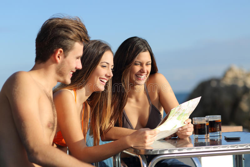 Vrienden die op vakanties een gids in een hotelterras raadplegen stock afbeeldingen