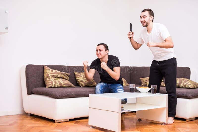 Vrienden die op voetbalwedstrijd op TV thuis met overwinningsschreeuwen letten stock foto