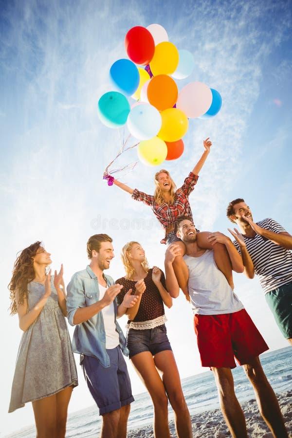 Vrienden die op zand met ballon dansen royalty-vrije stock afbeeldingen