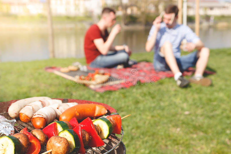 Vrienden die openluchtbarbecue hebben Grill met diverse barbecue, selectieve nadruk royalty-vrije stock foto