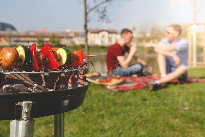 Vrienden die openluchtbarbecue hebben Grill met diverse barbecue, selectieve nadruk stock afbeelding
