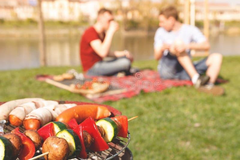 Vrienden die openluchtbarbecue hebben Grill met diverse barbecue, selectieve nadruk stock fotografie