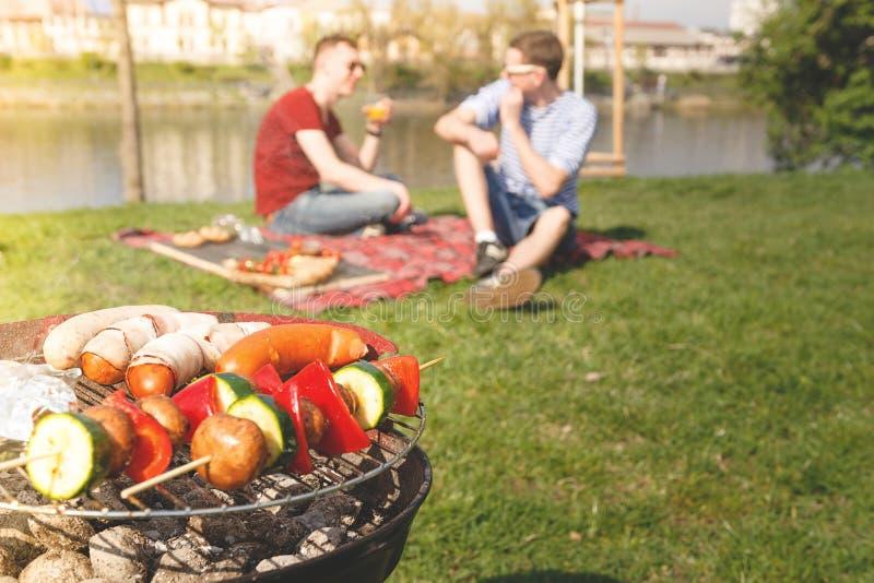 Vrienden die openluchtbarbecue hebben Grill met diverse barbecue, selectieve nadruk stock foto's