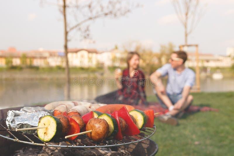 Vrienden die openluchtbarbecue hebben Grill met diverse barbecue, selectieve nadruk stock foto