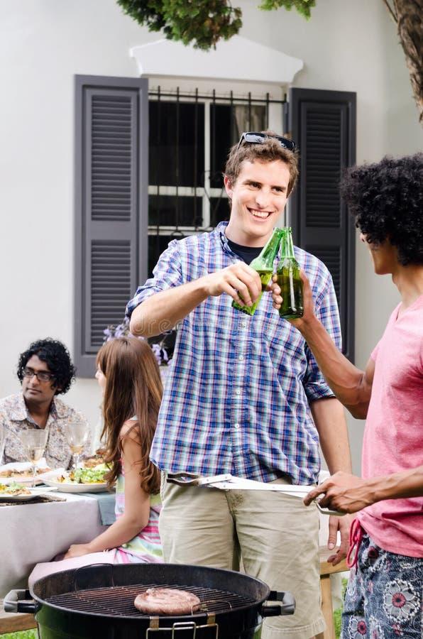 Vrienden die over bbq met in hand bieren plakken stock foto's