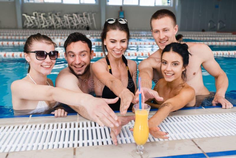 Vrienden die partij hebben en emmers drinken bij een zwembad stock foto's