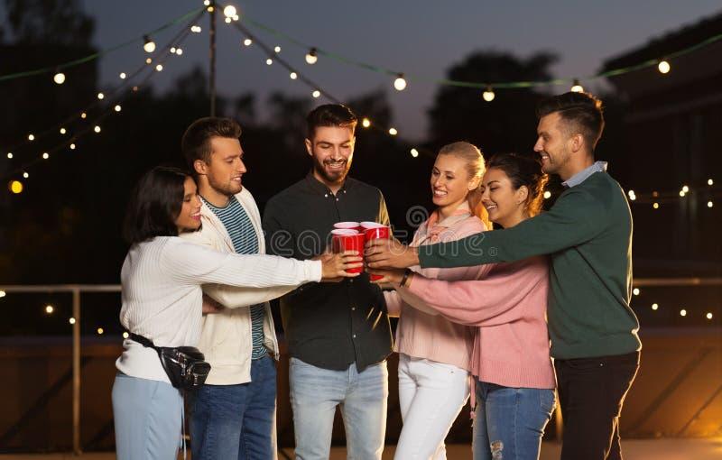 Vrienden die partijkoppen op dak clinking bij nacht stock afbeeldingen