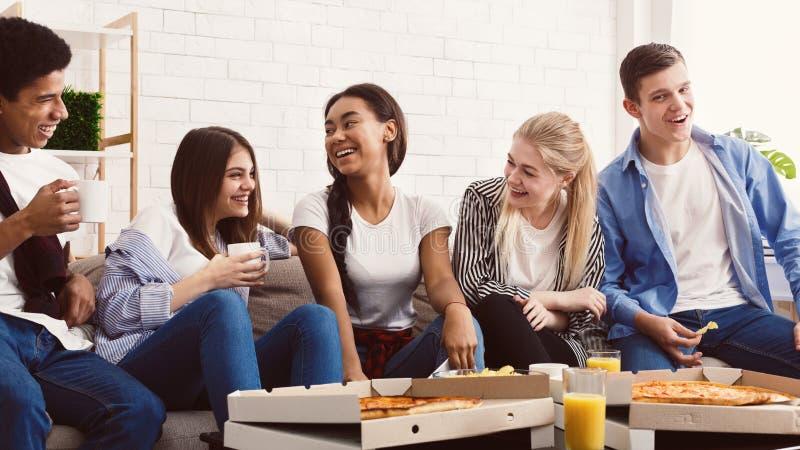 Vrienden die pizza eten Tieners die pret thuis partij hebben stock fotografie