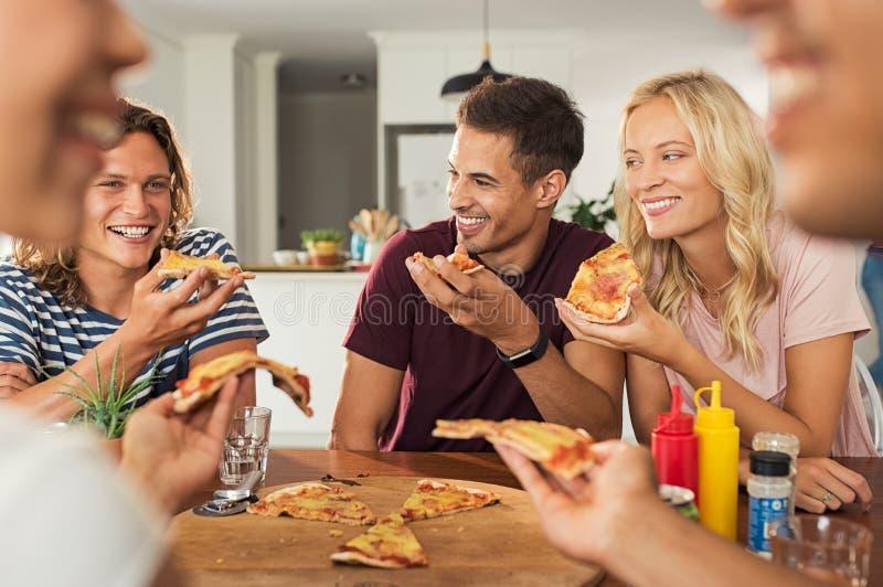 Vrienden die pizza thuis eten royalty-vrije stock afbeeldingen