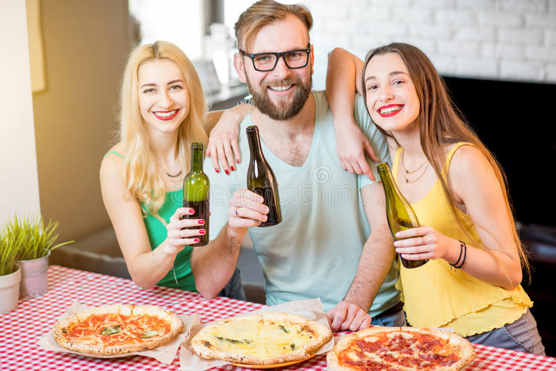 Vrienden die pizzapartij hebben thuis stock afbeelding