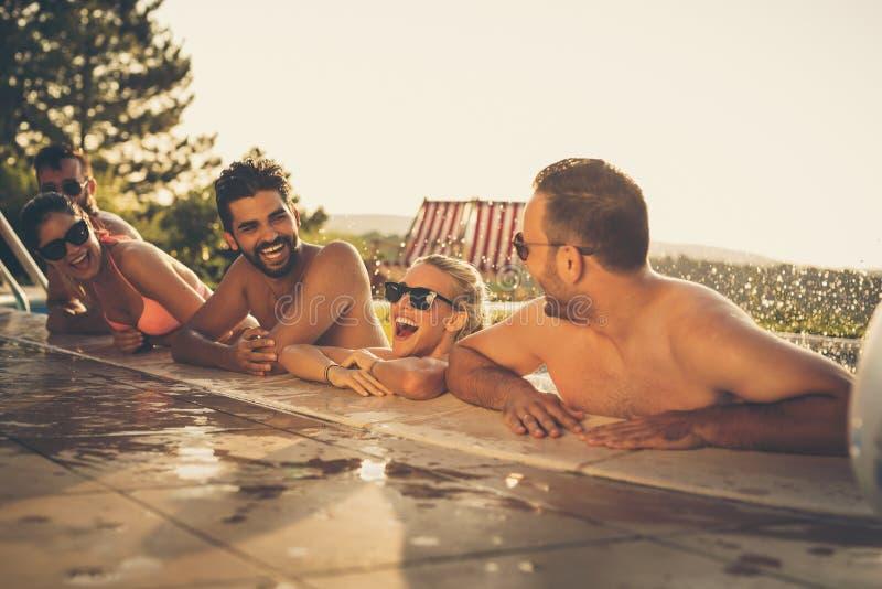 Vrienden die pret hebben bij de pool stock foto's