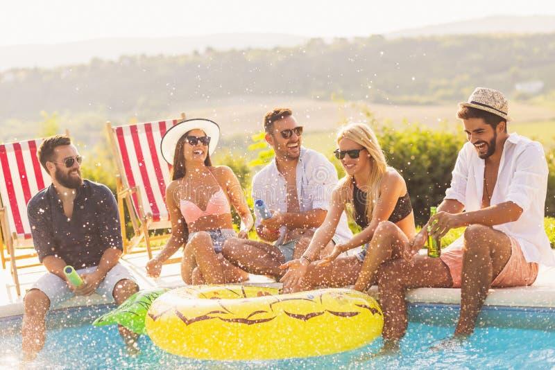 Vrienden die pret hebben bij een poolsidepartij stock fotografie