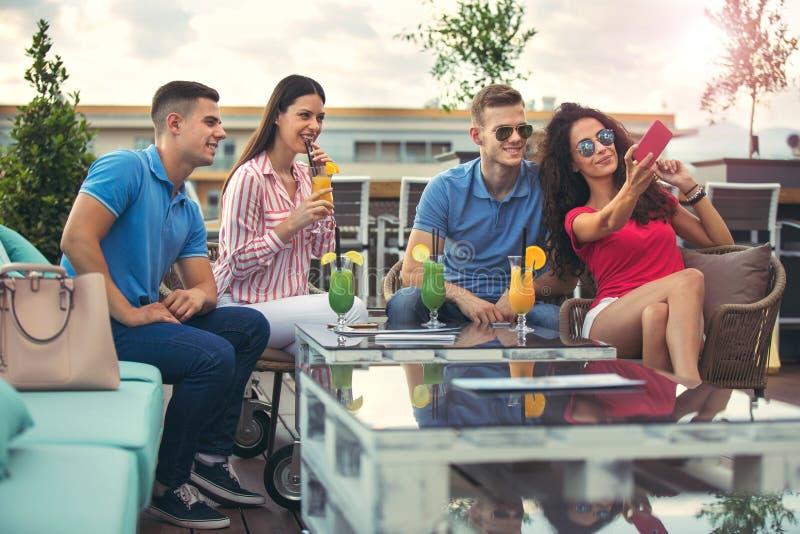 Vrienden die pret hebben en cocktails drinken openlucht stock afbeelding