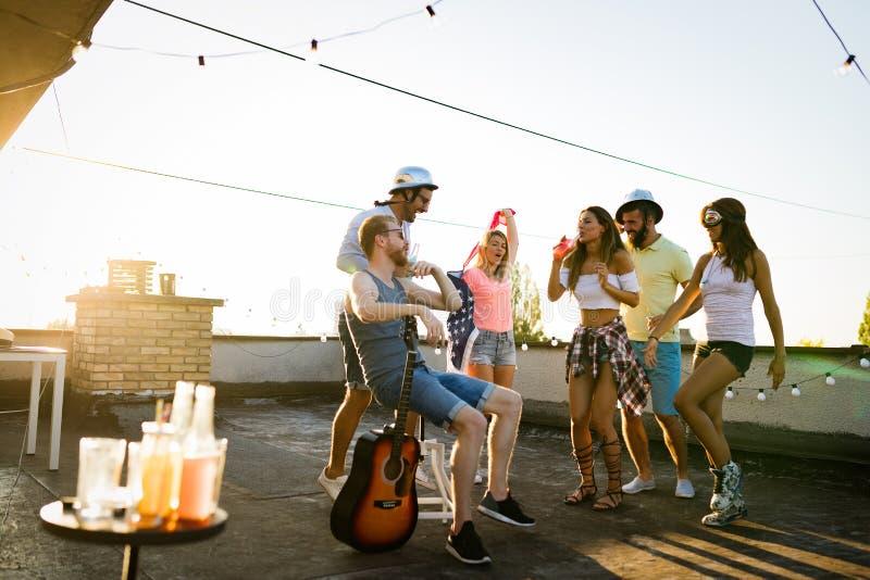 Vrienden die pret hebben en cocktails openlucht op een dakbijeenkomst drinken royalty-vrije stock afbeelding