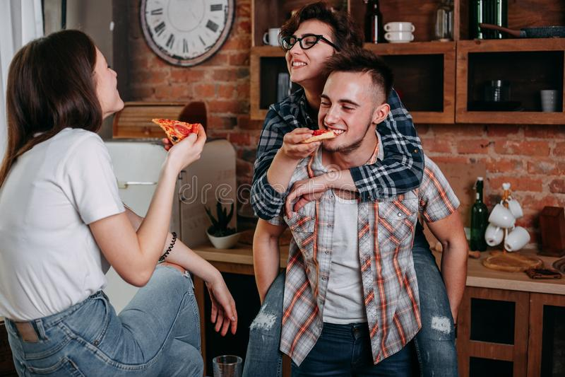Vrienden die pret hebben en pizza thuis partij eten stock foto's