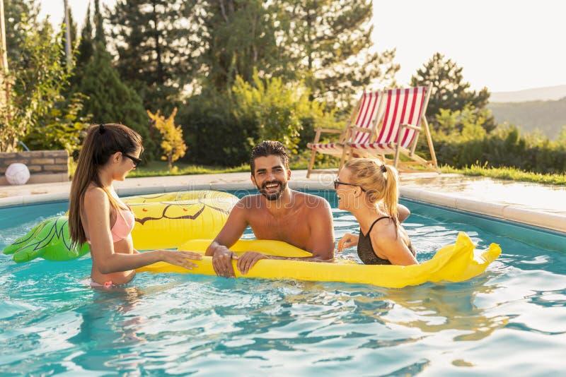Vrienden die pret in het zwembad hebben royalty-vrije stock afbeeldingen