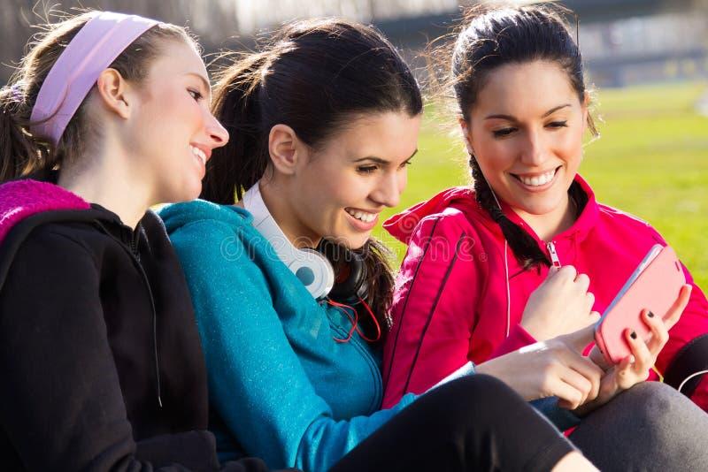 Vrienden die pret met smartphones na oefening hebben royalty-vrije stock afbeeldingen