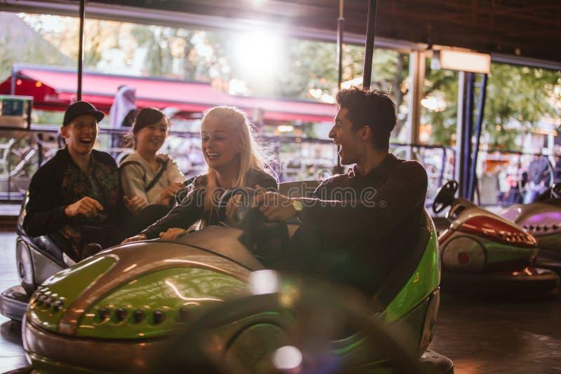 Vrienden die pret op bumperauto's hebben in pretpark royalty-vrije stock foto