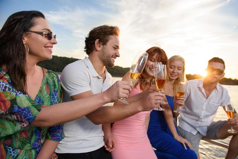 Vrienden die pret op jacht hebben en champagne drinken stock afbeelding